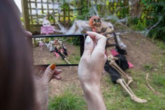 woman taking picture of skeleton yard decoration
