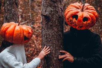 couple wearing pumpkin costume hiding behind tree