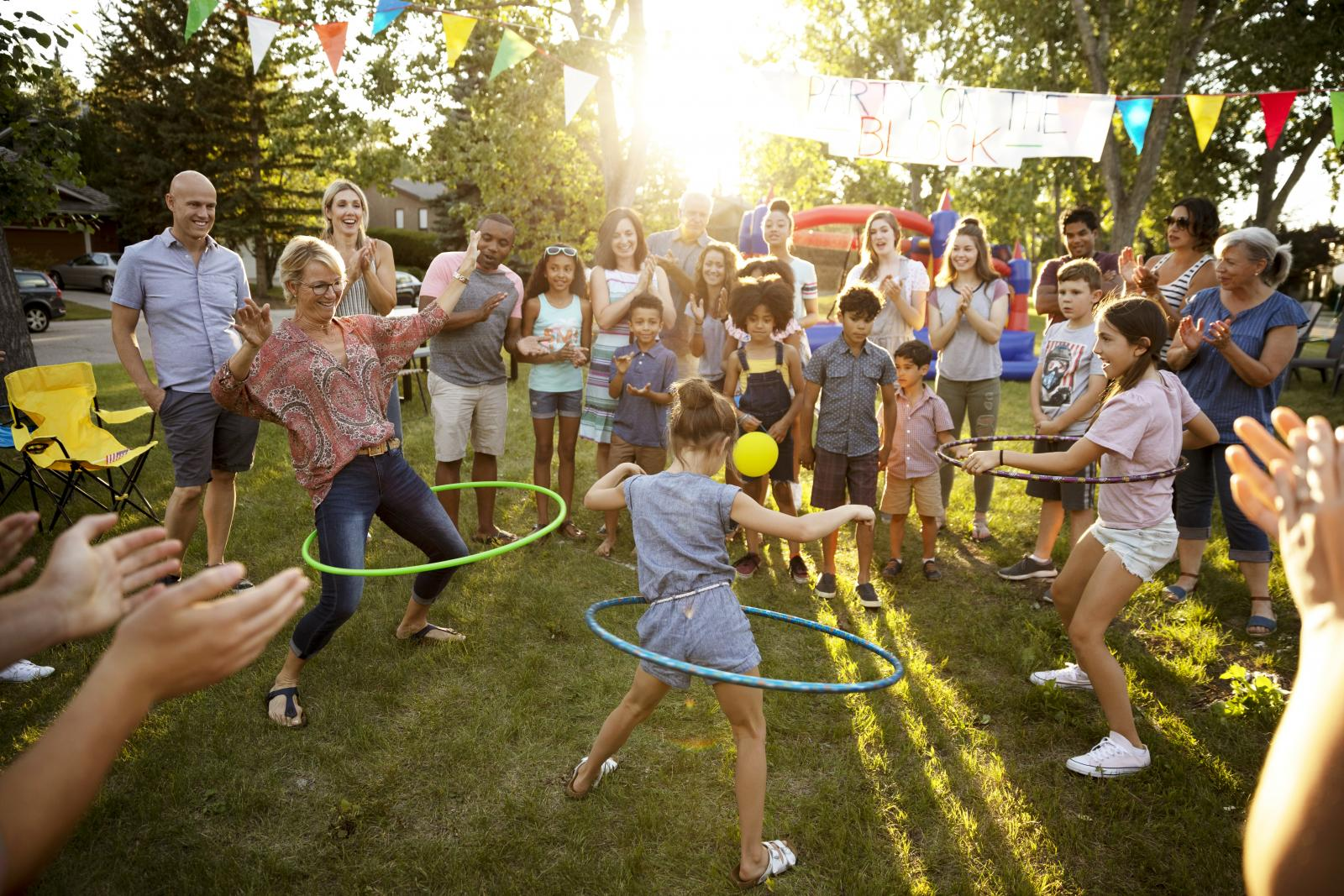 Neighbors spinning in plastic hoops at summer block party in park