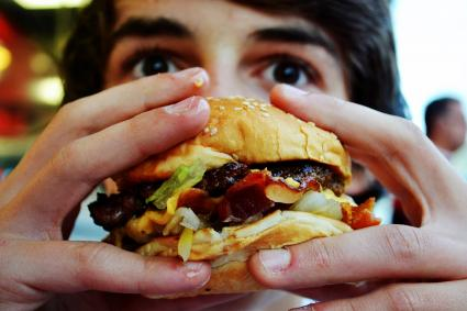 Teenage Boy Eating Hamburger