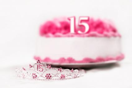 A tiara worn by a girl celebrating her 15th birthday is shot in front of a birthday cake