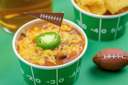 Superbowl chili, beer, and party snacks on green field