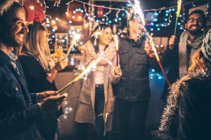 Friends, at an outdoor New Year's celebration, lightning sparklers at midnight