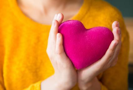 Teenager Holding Pink Heart Pillow