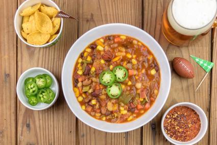 Vegetarian chili and mug of beer with football theme