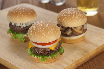 Three sliders on cutting board with beer