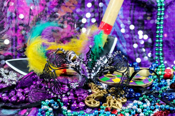 Mardi Gras Carnaval background with black filigree mask, beads, and feathered bamboo spears