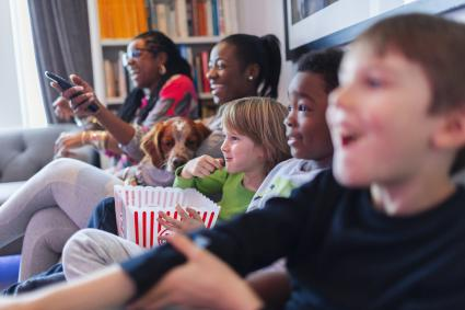 Multi-ethnic family watching movie and eating popcorn