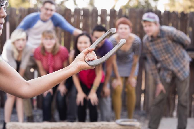 Friends watching woman play horseshoe in backyard