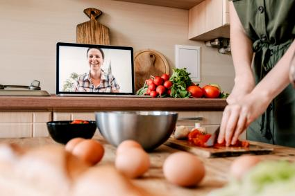 Woman cooking Thanksgiving dinner and talking online with family