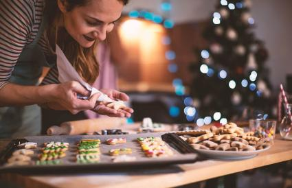 woman decorating cookies for Christmas