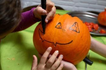 kid drawing on a pumpkin