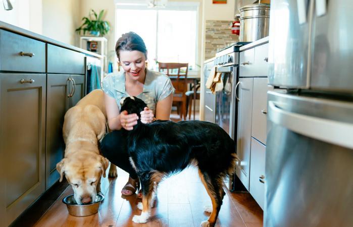Mujer dandole de comer a sus perros