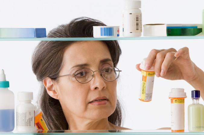 mujer mirando medicamentos recetados