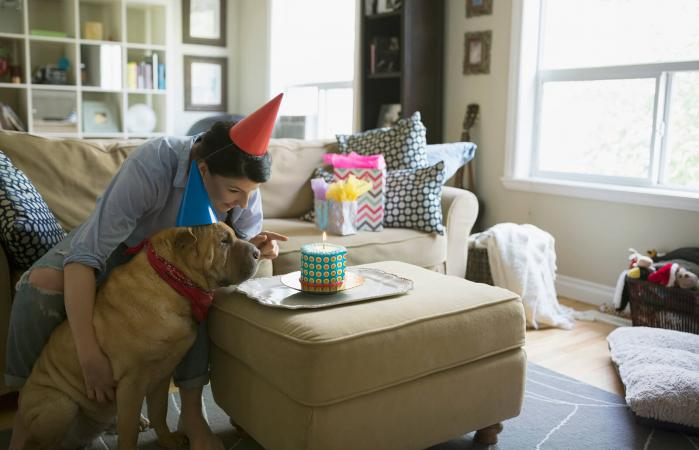 Mujer y perro celebrando su cumpleaños con pastel