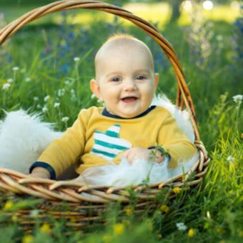 Baby sitting in a wicker basket outside
