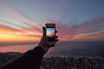 Hand Photographing Sunset On Mobile Phone
