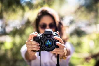 Woman wearing sunglasses holds a DSLR camera in front of her