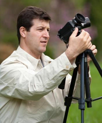 Man using a camera tripod