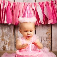 Birthday baby with cake and fabric streamers in background