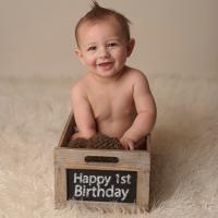 Baby in box with Happy 1st Birthday sign