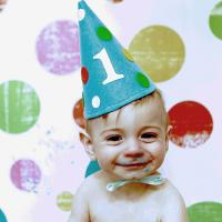 Baby wearing first birthday party hat