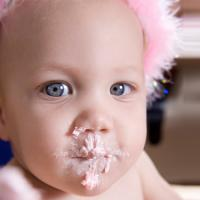 Photo of baby with cake frosting on her mouth