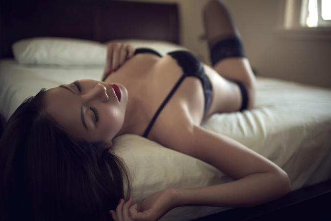 Woman wearing black lingerie in bed