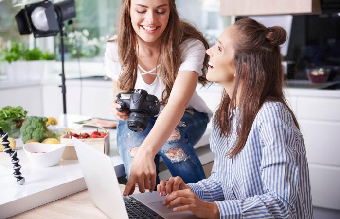 Happy women using laptop in kitchen