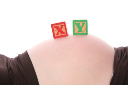 Woman's baby bump with X and Y blocks