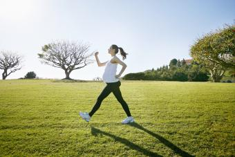 Pregnant woman exercising in field