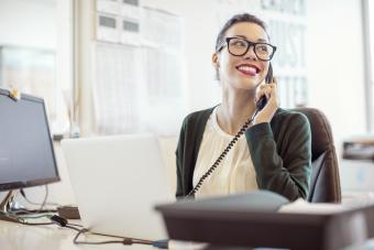 Businesswoman talking on landline phone