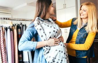 Pregnant woman trying maternity clothes