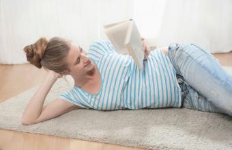 Pregnant woman relaxing carpet reading book