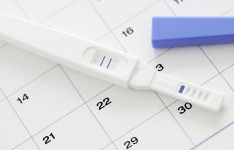 Pregnancy test showing positive result and calendar