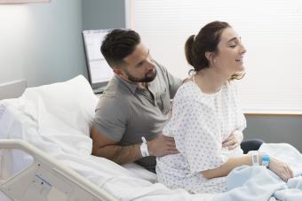 Man massaging partner's back during active labor