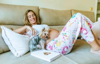 Pregnant woman and dog lying down