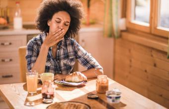 woman feeling nausea during breakfast time