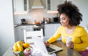 Woman using laptop at home and drinking coffee