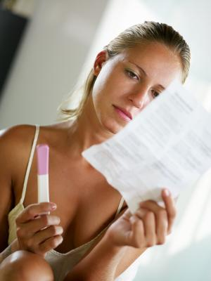 Woman reading the instructions before taking a pregnancy test
