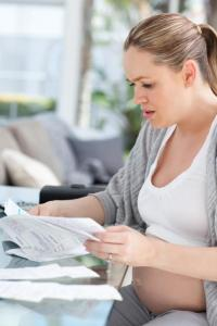 pregnant woman worrying about bills
