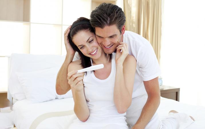 Happy couple looking at a pregnancy test result