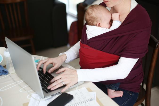 woman typing with baby
