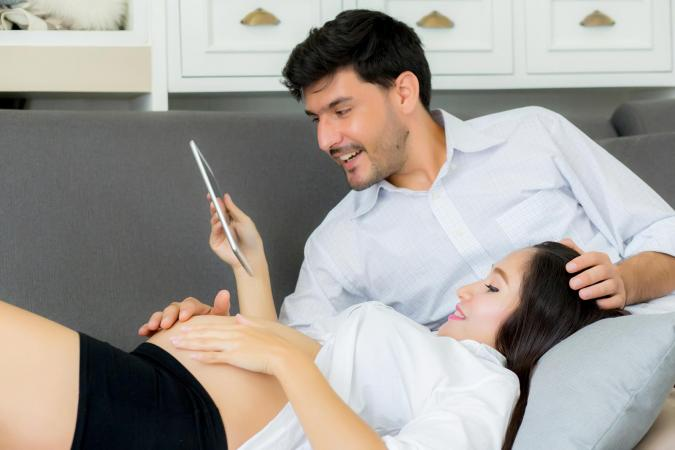 pregnant couple watching video on tablet