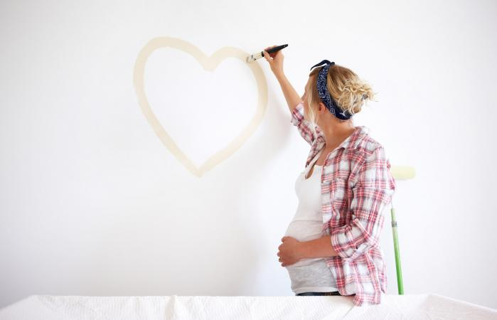 Pregnant woman painting a wall