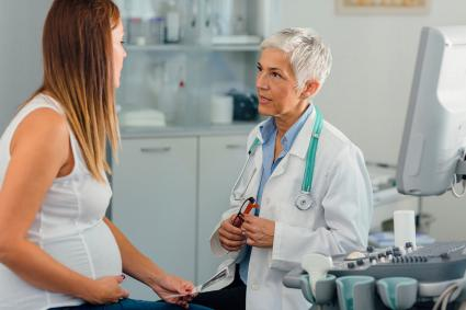 Pregnant woman consulting with doctor