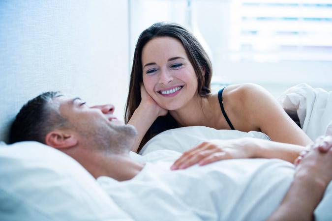 Smiling couple laying in bed talking