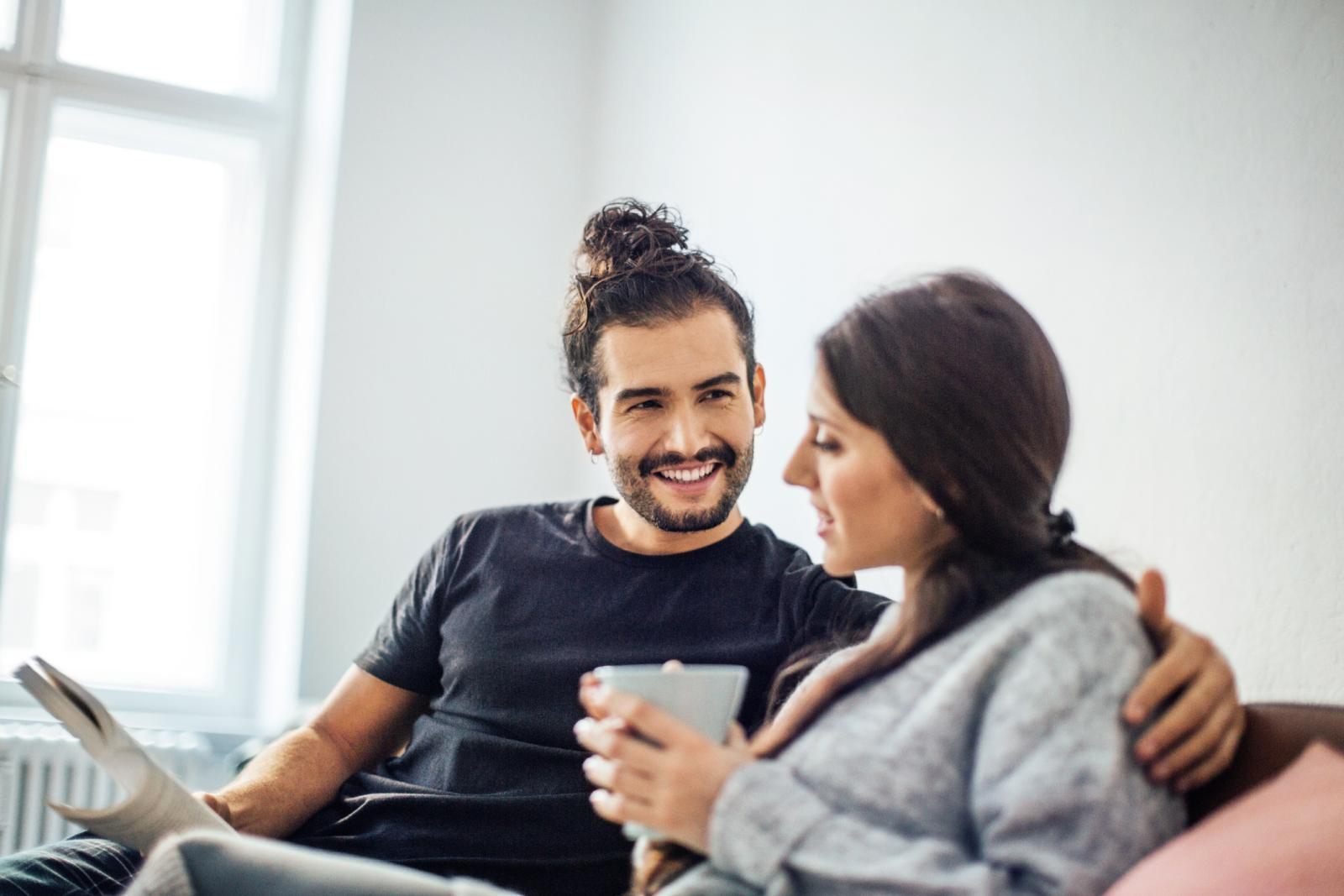 Man holding a book while looking at woman having coffee