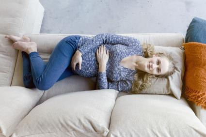 Smiling pregnant woman lying on couch at home