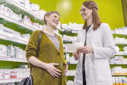 Pharmacist advising pregnant woman in pharmacy